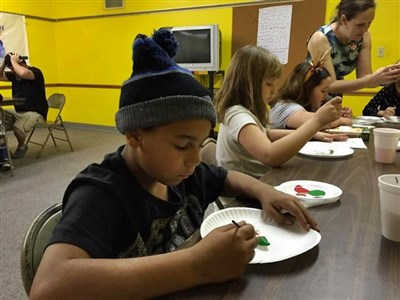 Kids work on a craft project with paper plates at Community UMC Casselberry