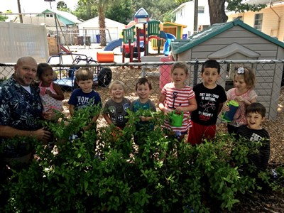 First UMC Pastor Mike Briggs with preschool kids and their Earth Day plantings from 2014