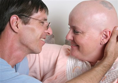 Man looks lovingly at woman in gown who has lost hair due to chemo