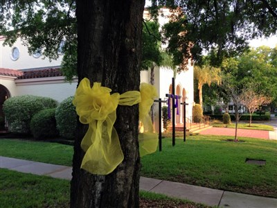 Large yellow ribbon tied around an oak tree outside a church sanctuary