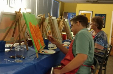 Two people share a table where they participate in a social painting event.