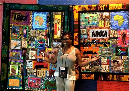 Rev. Juana Jordan stands in front of a colorful quilt showing scenes from Africa