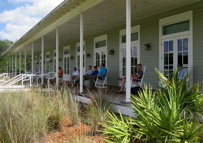 Extension ministry directors relax in rocking chairs on a porch