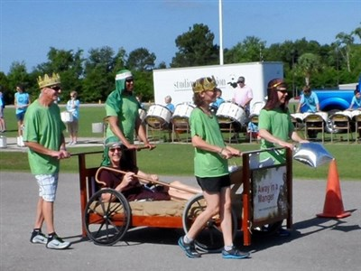 Trinity UMC team pushes bed with wheels and Pastor Dan Johnson riding