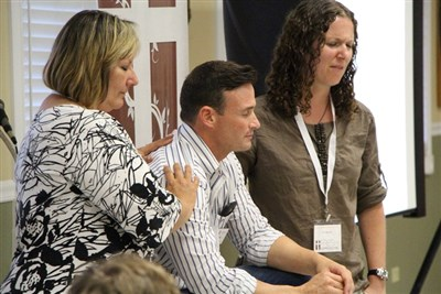 Patti Aupperlee prays with Chad Stoffel and Kris Beckert