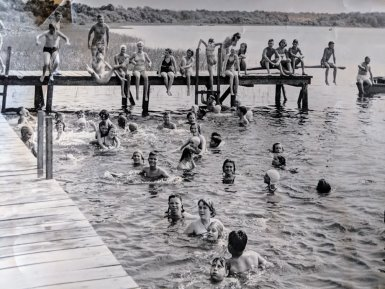 Old black and white photo of campers swimming together
