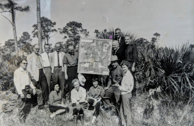 black and white photo of a group of men posing with the blueprints of a new religious campsite