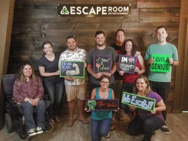 Food for Thought participants hold up self-congratulatory signs after completing the Escape Room challenge.