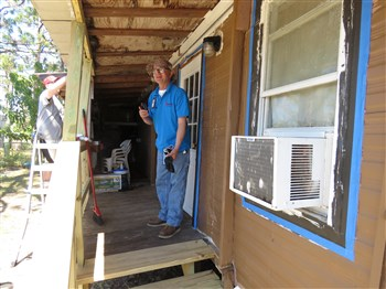 FLUMC construction coordinator Paul Crotty stands on the porch, near the new steps, while Evan Brinnon paints trim at left.
