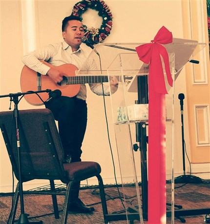 Adrian Vera Baez plays a guitar in worship at St. John's by the Lake in Miami Beach