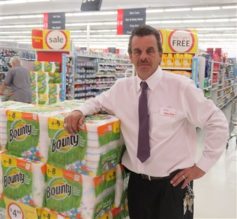 Kenny Lowe a Winn-Dixie store manager standing on the storeroom floor next to a stack of paper towels