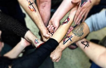 Picture of people showing off the UMC logo tattoo on their wrists.
