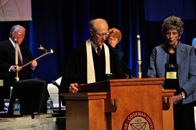 Rev. Bob Tindale at podium with Nell Thrift at sice