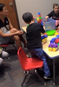 A child works with Legos as an older woman helps sort them