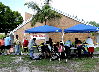 Adults and children lined up at registration tables in front of a church Welcome sign