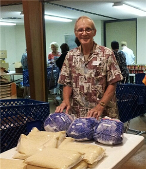 Older adult male volunteer sorting turkeys at food pantry