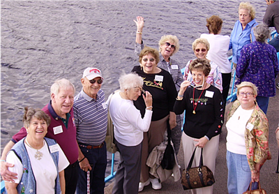 Happy seniors waving from a boat cruise