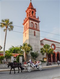Horse-drawn carriage bearing tourists passes imposing Grace UMC in St. Augustine