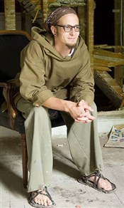 Shane Claiborne sitting in chair in rustic setting