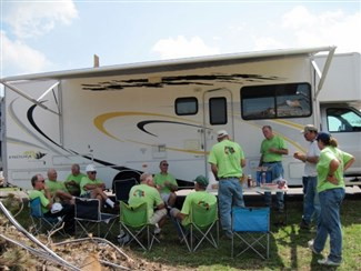Volunteers in green disaster recovery shirts have lunch with a storm victim in front of RV