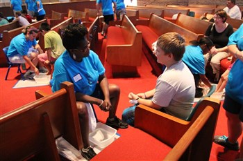 Volunteers at Indian River City UMC wash feet as part of a shoe giveaway for students