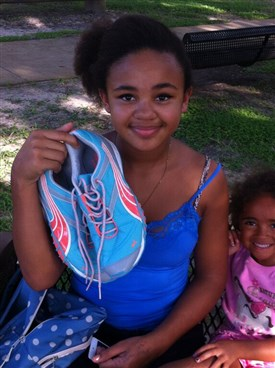 Preteen girl holding up new pair of shoes