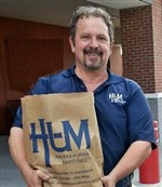 Mark Geallis holding paper grocery bag marked with letters HUM