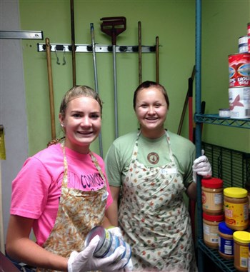 Two girls working in a food pantry
