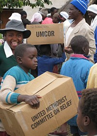 Children and adults in Zimbabwe happily unload boxes labeled UMCOR