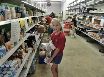 A preteen girl stocks grocery shelves with older volunteers working in the background