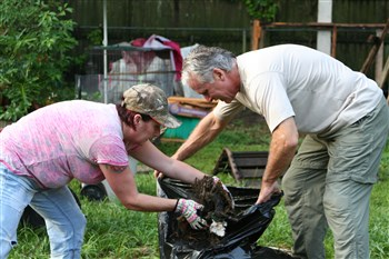 Alicia Barbarini and Tom McDonough from Cork UMC pull debris from a firepit