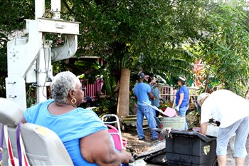 Homeowner Rosemary Brown watches volunteers work at her house from her wheelchair
