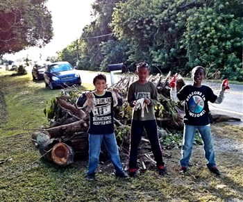 Three Cub Scouts from South Shore UMC show off debris they collected during CareFest