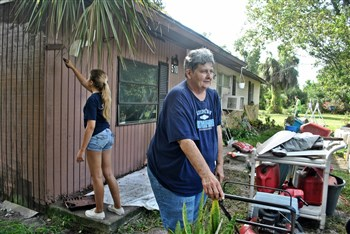 Darlene Compton in front of her home with volunteers working behind her
