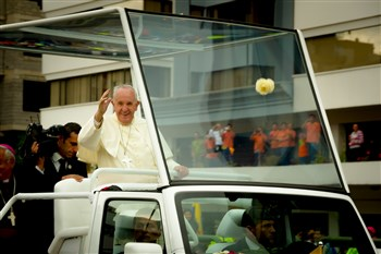 Pope Francis waving at crowds from the Popemobile