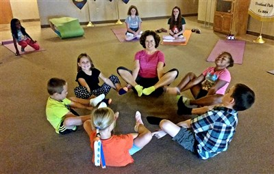 Adult volunteer leads exercise circle of kids at Fruitland Park church