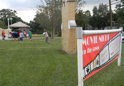 Kids run and play in background behind movie night sign