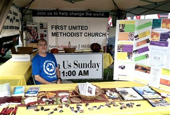 Pastor Will Clark staffs a booth at the local Peanut Festival