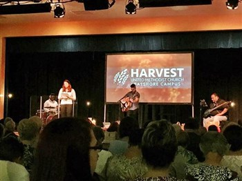 Praise band in front of Harvest Bayshore sign at church launch service