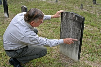 Jim Smith looks for the date on a headstone in Wacahoota cemetery