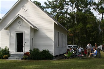 Worshipers in lawn chairs receive communion outside Wacahoota UMC
