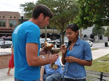 Pastor Michael Beck offers communion sacraments to Nancy Ortiz in Ocala downtown square