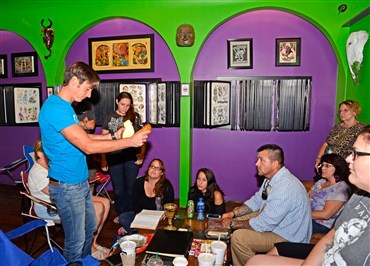 Pastor Michael Beck breaks bread for communion at tattoo parlor study group