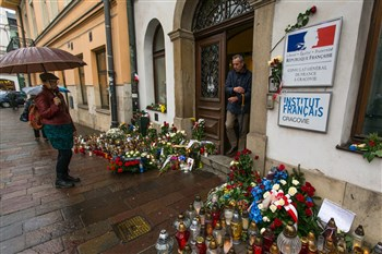 People viewing lamps and flowers in front of French office in Krakow, Poland