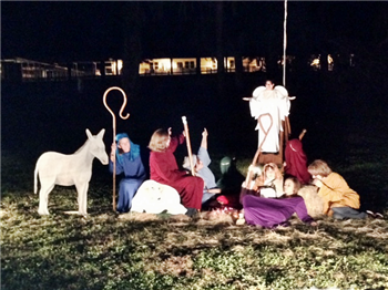 Lighted living nativity scene against dark sky