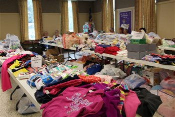 Piles of clothes on tables in the Manatee UMC fellowship hall