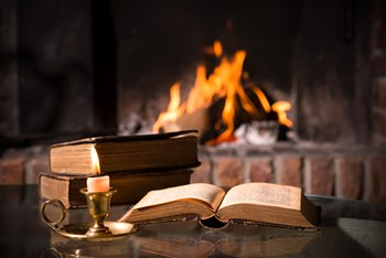 Open Bible in front of flames in fireplace