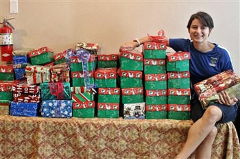 Youth ministry director Melissa Hernandez with piles of shoebox gifts for shipping