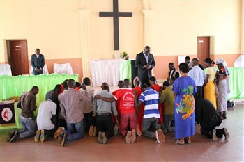 Dr. Simon Osunlana prays during a gathering at the Quessua mission church