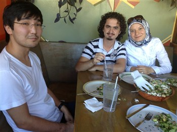 From left, young man named Berik, Muharrem and Ozlem Ayar at a table
